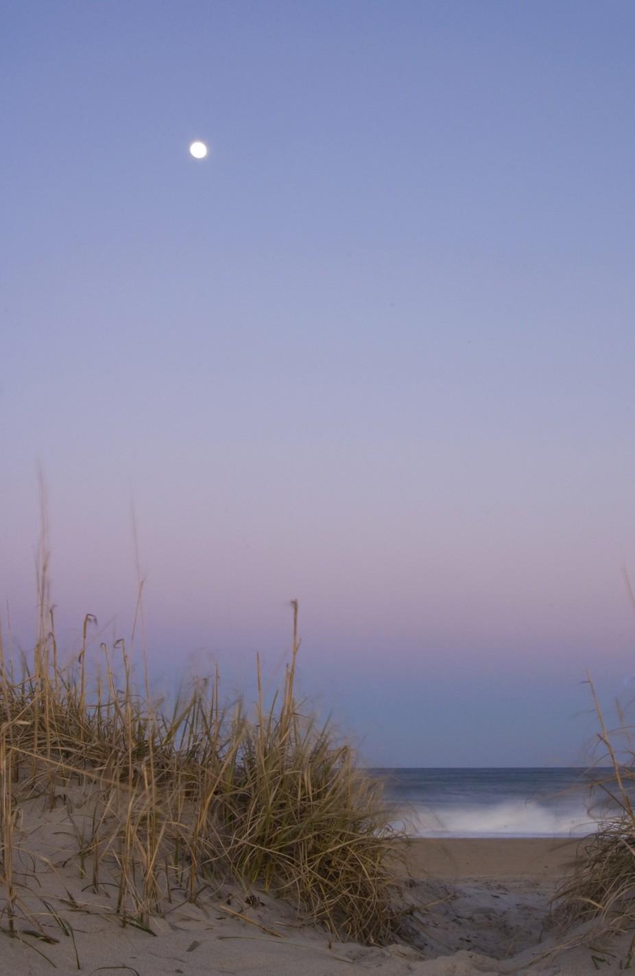 A nearly full moon rises above the Atlantic Ocean at Buxton, North Carolina