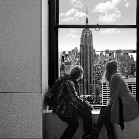 A young couple at the Rockefeller Center enjoy the view of the Empire State Building and the New York City skyline.