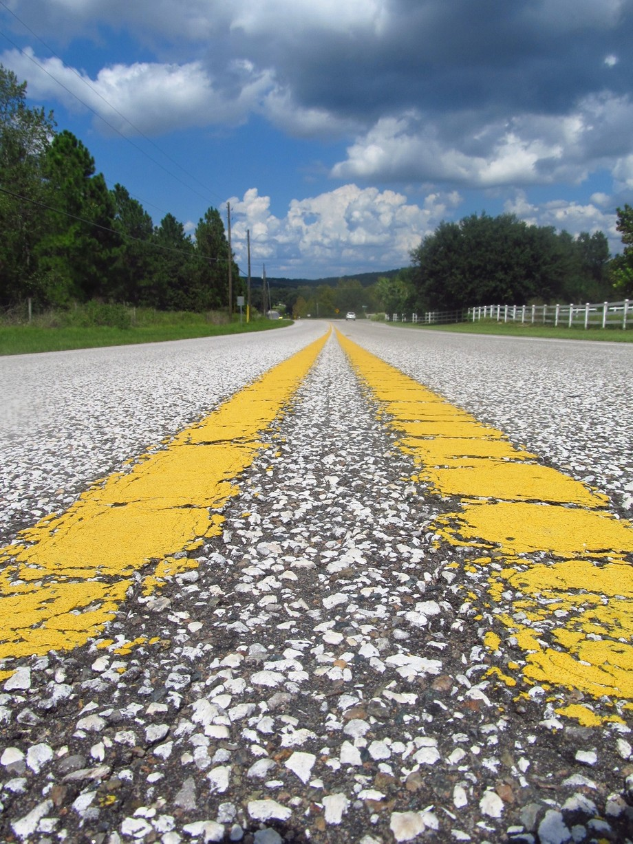 A picture of the double yellow lines on the road outside my neighborhood.
