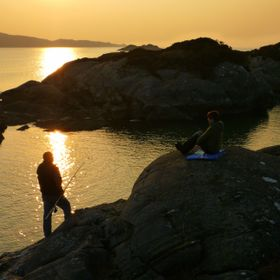 A married couple on a romantic weekend fishing trip in the Scottish Highlands, as the sun sets.