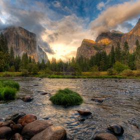 Clouds clear over the Merced River in Yosemite Valley after a storm.