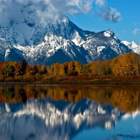 With its summit shrouded in clouds, Mount Moran is reflected in the still water of the Snake River at Oxbow Bend on a cool fall morning in Grand ...