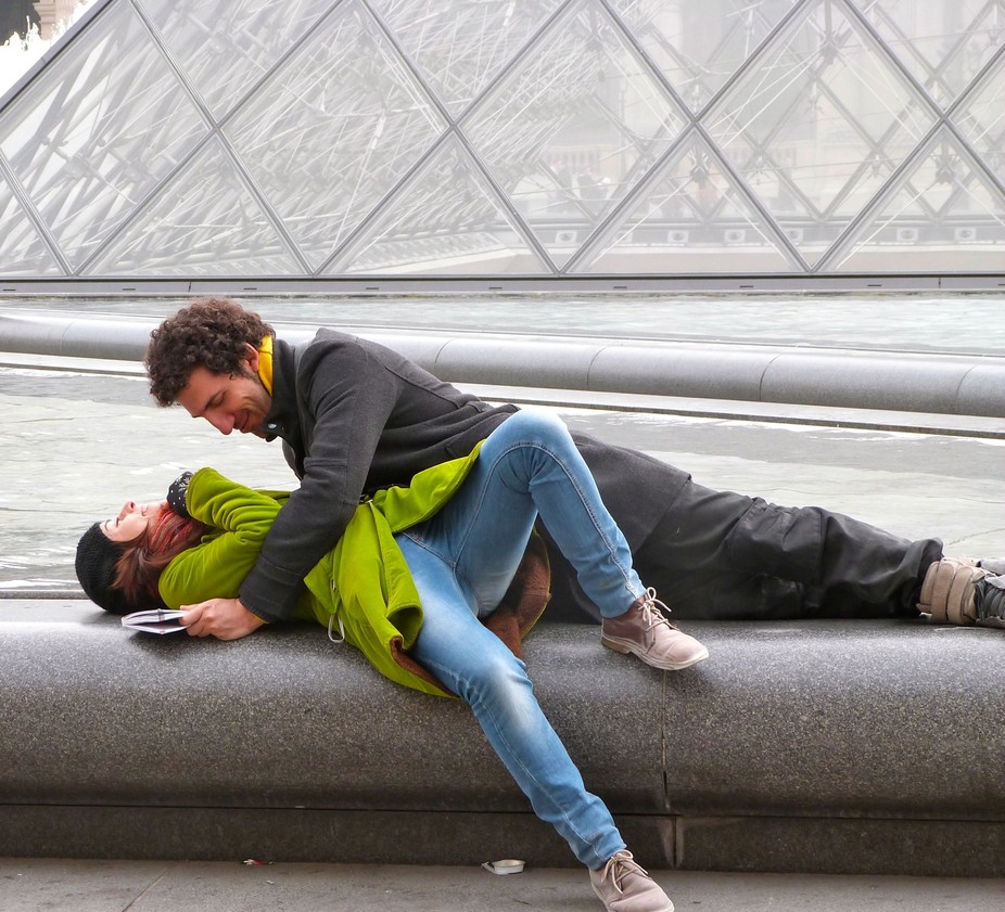 april in paris lovers in motion in front of Louvre pyramid april 2012