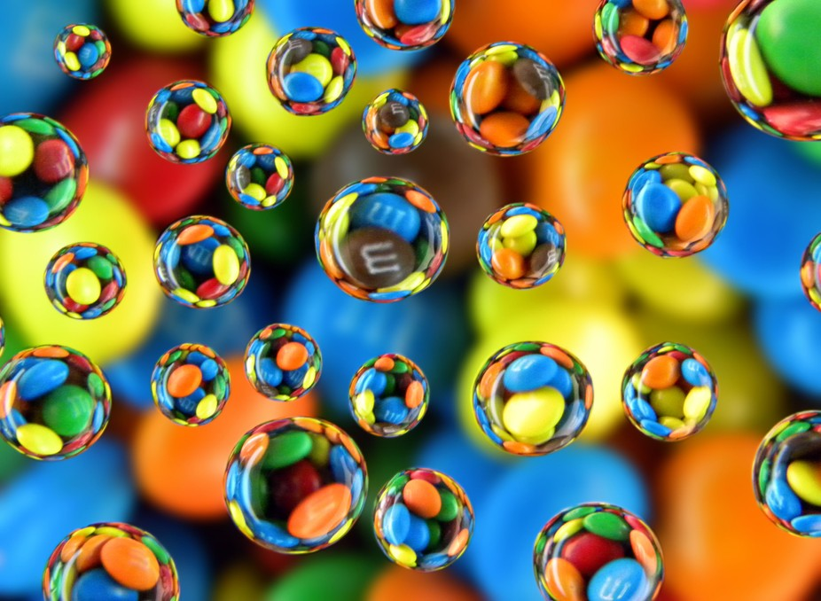 Water drops on a pane of glass refracting mini M&M\'s