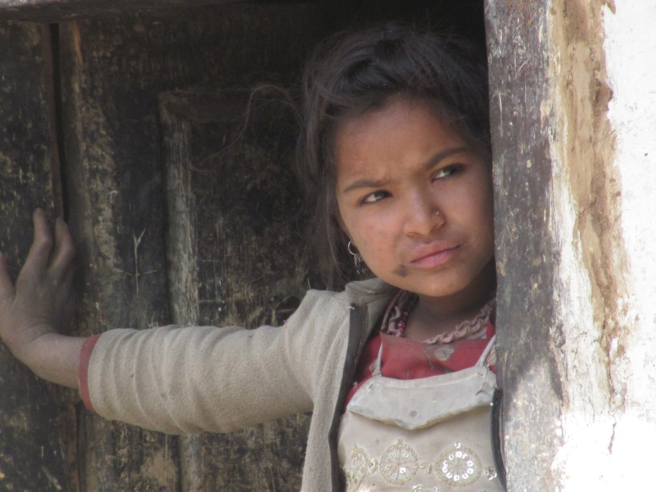 A girl watching the worker of NGO who come to her house from the door in Rini Village of patmara ...