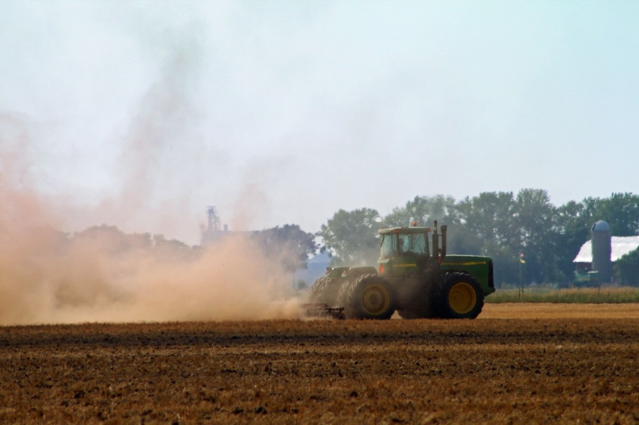 A farmer creating a cloud of dust while plowing his dry field.