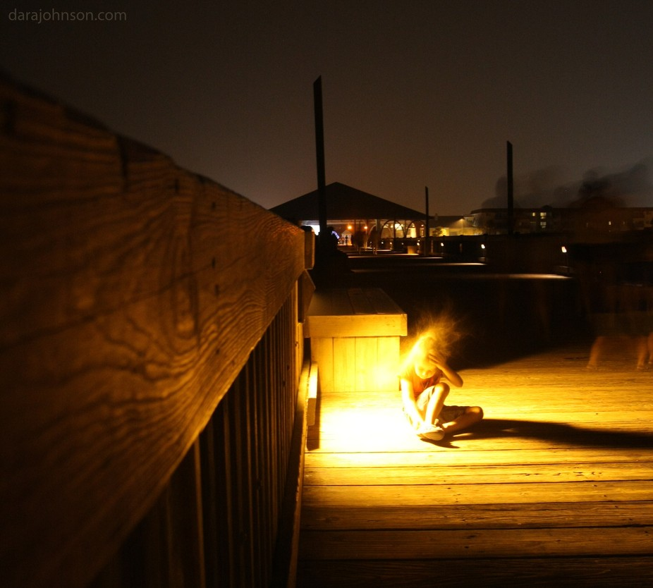Long exposure of red haired girl sitting on the pier at Tybee Island, Georgia on a windy night.