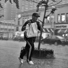 A boy running through the streets of New York trying to escape the sudden storm did not dampen the shopping bag of.
