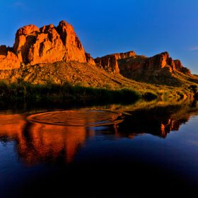 A jumping fish creates a ripple effect in the reflection of the jagged hills of the Salt River Canyon.
