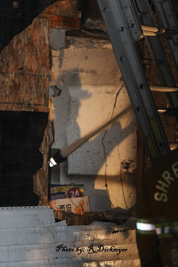 A firefighters shadow in an apartment putting the fire out with the hose.  The hose and water are...