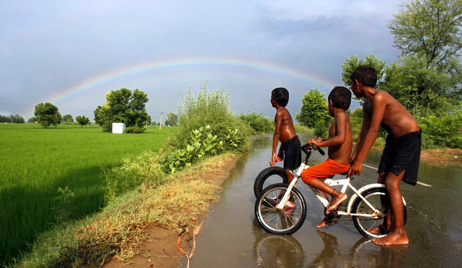 The tiny tots of border village near Pakistan Border gazing at rainbow as playing in rain in India.