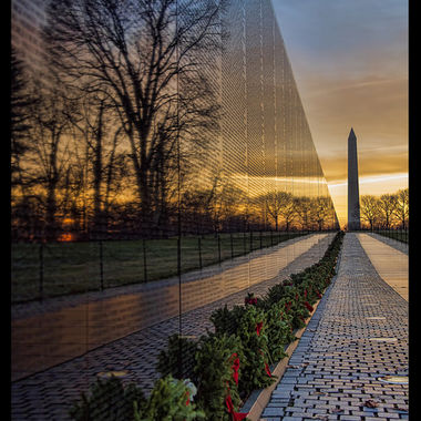 Sunrise reflection in the on the Vietnam War Memorial - with the Washington Monument and Wreaths across America