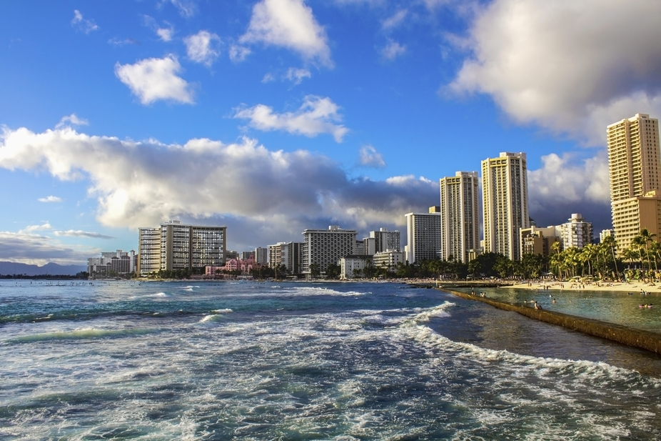 Large clouds fill the vibrant blue skies above Hawaii, wrapping themselves around the skyscrapers...