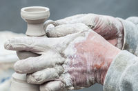 Hands creating pottery