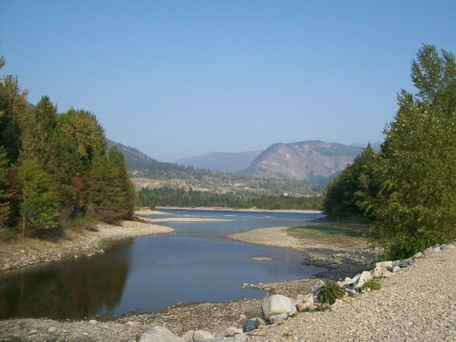 An inlet, convergence of 2 rivers and mountains in the background
