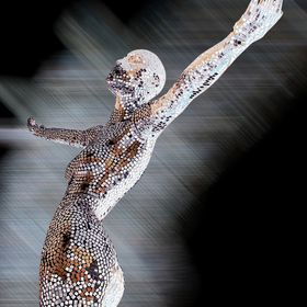 A mirror-mosaic statue of a female nude sparkles triumphantly in a shop window in Christchurch, New Zealand.