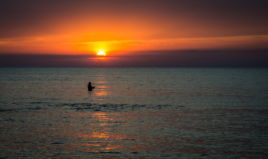 Fisherman at sunset, looking for that big catch