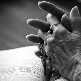 A black and white shot of a senior woman's hands praying on the bible holding her rosary.