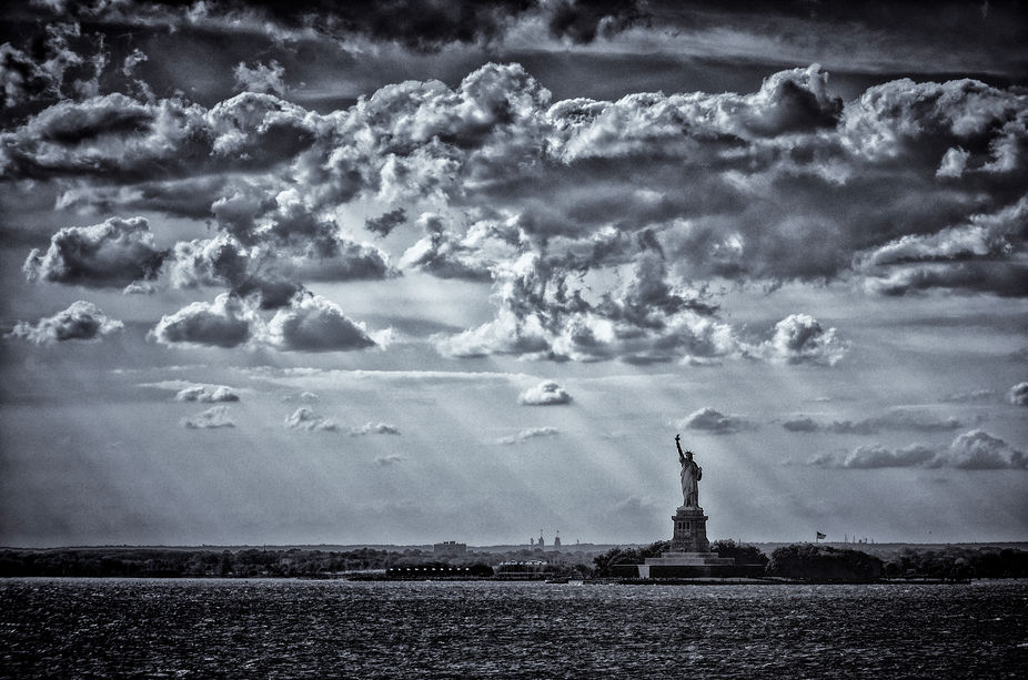 Beautiful sunlight cutting through    fluffy clouds, casting light upon our famous Statue of Libe...