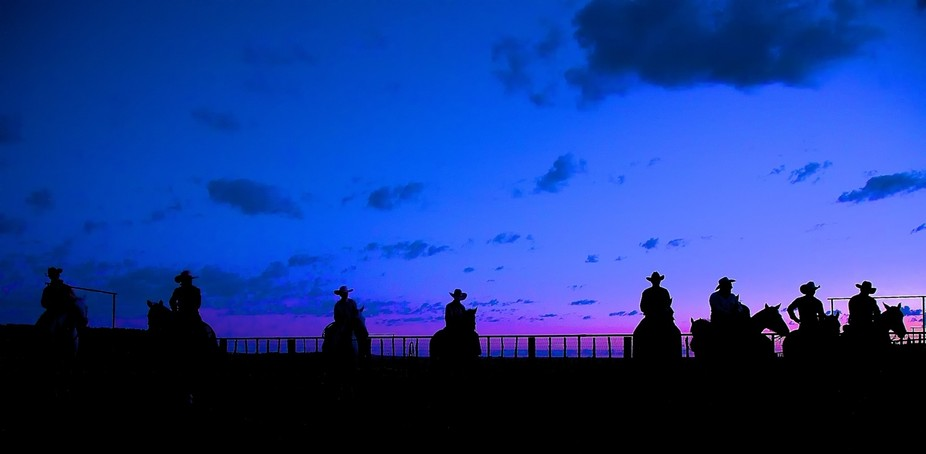 Early morning at the 06 Ranch and the cowboys line up waiting to ride off for round-up.