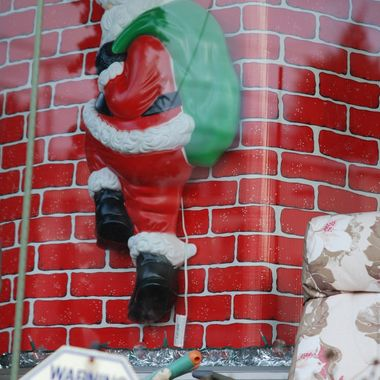Indoor Santa decoration showing him climbing out the fake chimney.
