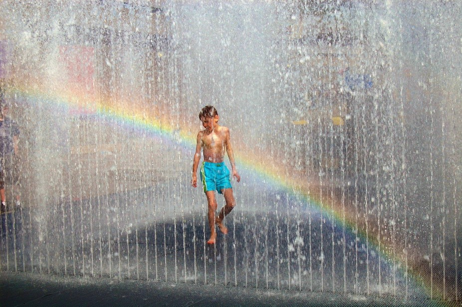 A boy plays in a fountain in London.
