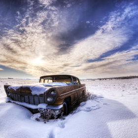 An old abandoned Lincoln car sits in a field for another winter.
