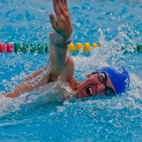 A close up of a swimmer turning his head to take breath during a swim meet.