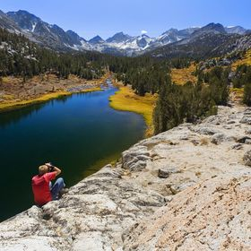 A photographer captures an image from a rock ledge overlooking Mack Lake and the trails, trees, and mountains within the John Muir Wilderness.