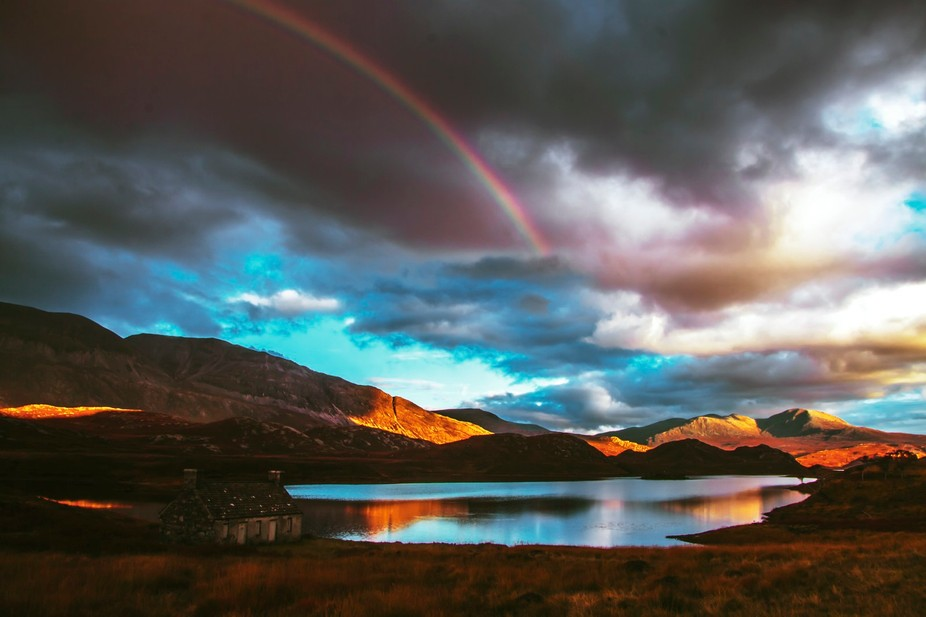 Lucky shot of a rainbow over Loch More Sutherland Scotland