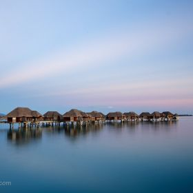 Bora Bora huts over the water after sunset.