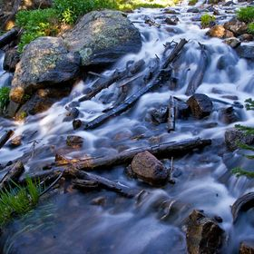 Swiftly flowing stream below Dream Lake in Rocky Mountain National Park, CO cascades over boulders and fallen logs.