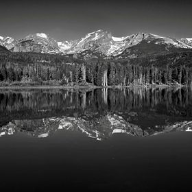 Otis and Hallet Peaks and Flattop Mountain along the Continental Divide are reflected in the perfectly calm early morning water of Sprague Lake i...