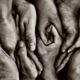 A family are united as one, with a show of hands. Monotone, with a slight sepia tone, to enhance.