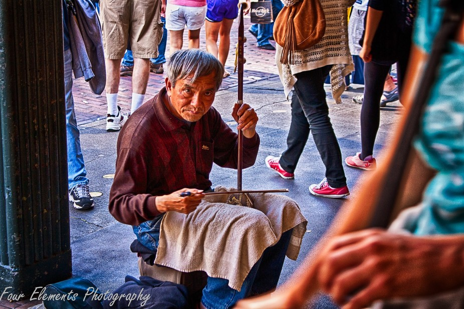 An elderly Chinese man playing a very old instrument I believe to be from one of the Dynasty\'s in...