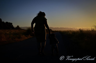 Mother teaching first steps to a child, during sunset