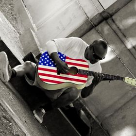 A man sitting alone in a corner of the park with his American flag guitar.