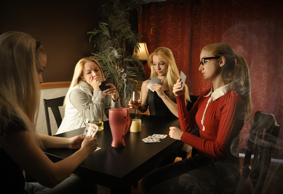 A woman with four different versions of herself is sitting at a table and playing cards. The wome...