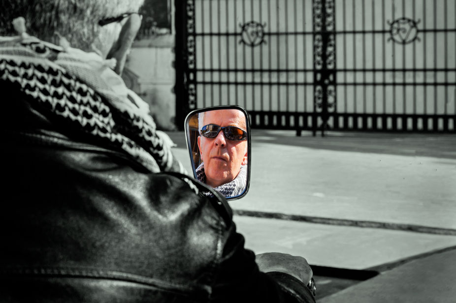 Vertical color portrait of face reflection of a Caucasian motorbiker in a rear view mirror waitin...