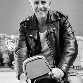 Color vertical portrait of a trendy fashion driven senior motor cyclist sat back to front on red cruiser smiling holding onto backrest. Generic s...