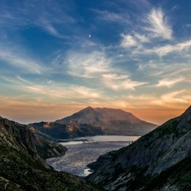 This photo was taken on a backpacking trip into the wilderness surrounding Mount St Helens. The moon can be seen above the mountain as the sun is...