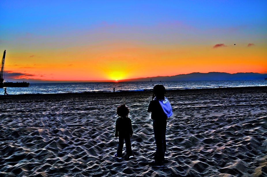 Sisters standing in Silhouette on the sand at Sunset.