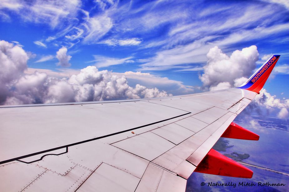 The blue sky streaked with white clouds is a nice background to the wing of this Boeing 737 flyin...