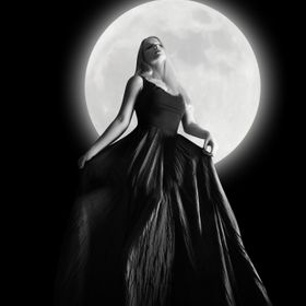 A woman is wearing a long black dress moving in the dark night against a full moon for a fashion or mystery concept.