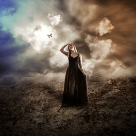 A young woman is wearing a black dress in a dark dry, nature landscape with a butterfly flying up to represent hope.