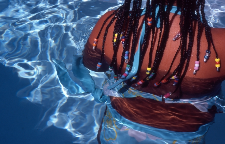 Color photograph of the back of a girl in a swimming pool with beads in her braided hair.