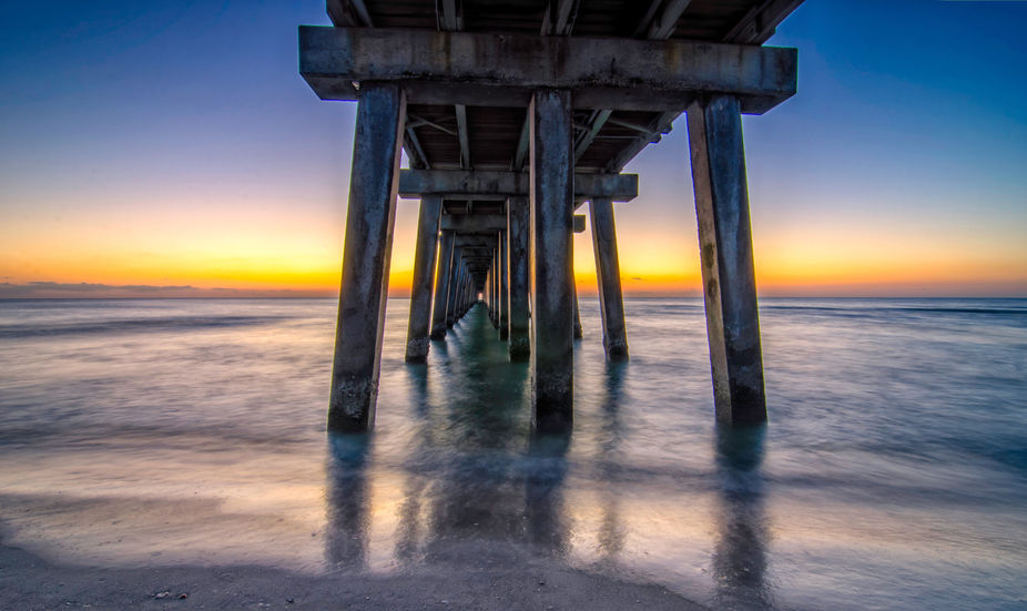Long exposure past sunset under the pier in Naples, Florida