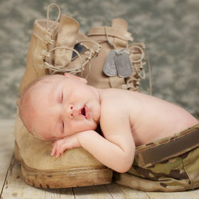 Sleeping Baby in army hat on Army Boot