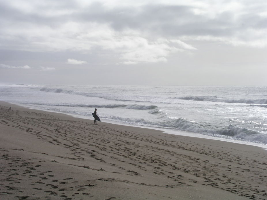 Half Moon Bay, California. Teen waiting for a perfect place to skim board along the shore.