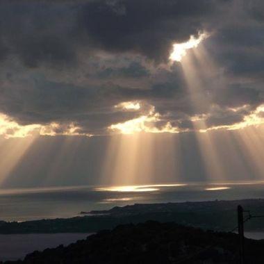 Sunrays pierce through cloud openings and illuminate sea.